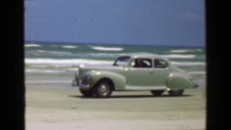 1952: Car driving on ocean beach sand in front of crashing surf waves.