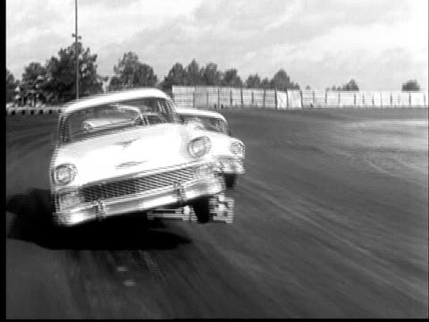 b/w rear pov 1956 car driving on race track, joie chitwood thrill show, usa - acrobazia video stock e b–roll