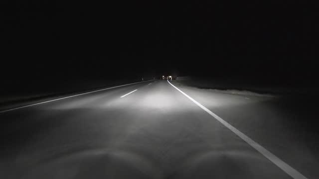 pov: auto fährt nachts auf der straße - autoscheinwerfer stock-videos und b-roll-filmmaterial
