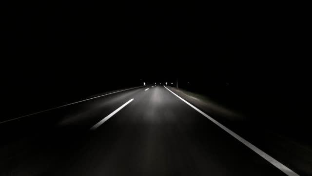 pov: car driving on road at night - fanale anteriore video stock e b–roll