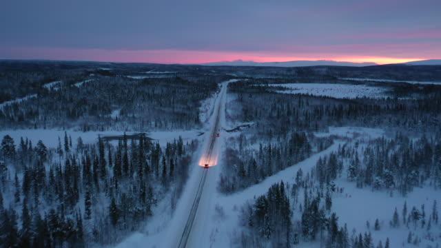car driving on rural road in winter season aerial view - snowing stock videos & royalty-free footage