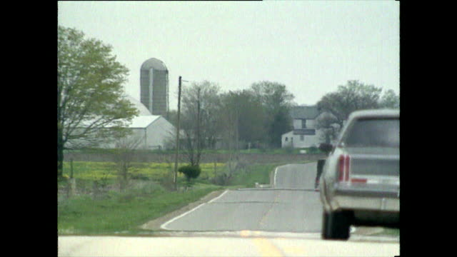 car driving on rural road towards farm; ohio, 1989 - uneven stock videos & royalty-free footage