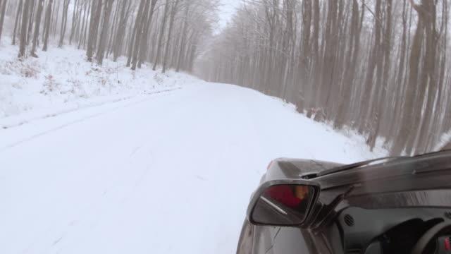 vidéos et rushes de véhicule pov conduisant sur la route couverte de neige, première chute de neige. - neige fraîche
