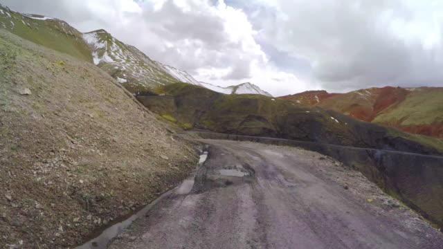 pov car driving on snowy and winding mountain road/qinghai,china. - 未舗装点の映像素材/bロール