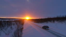 AERIAL: SUV car driving on snowy forest road at stunning golden winter sunset