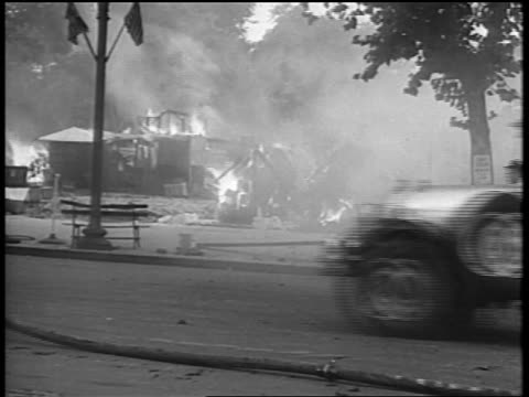 b/w 1932 car driving on street past burning veterans' camp / bonus march / washington dc - 1932 stock-videos und b-roll-filmmaterial