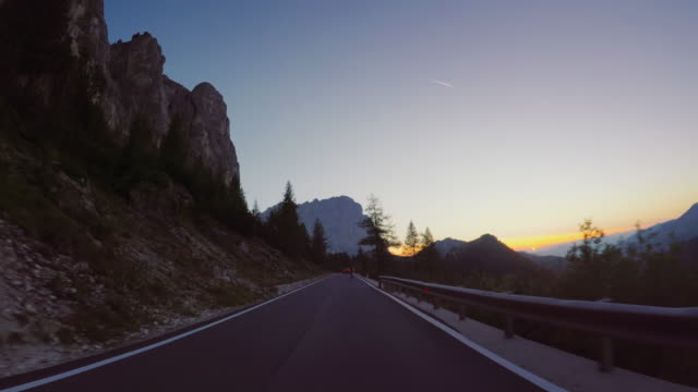vídeos de stock e filmes b-roll de pov car driving on the dolomites: mountain pass - pôr do sol