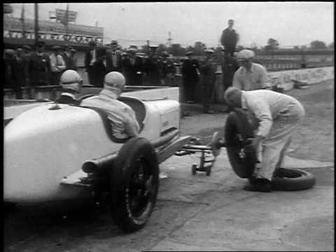 car driving on track into pit / crew changing front tires on car / car driving away - 1930 stock videos & royalty-free footage