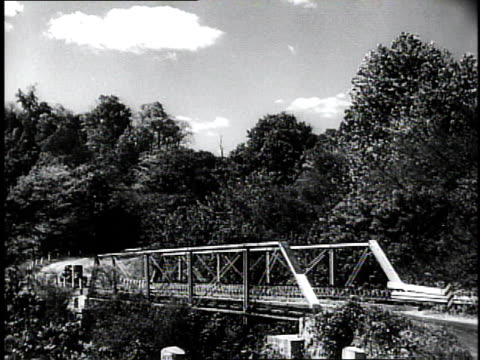 1950 ws car driving over a bridge on a country road / southville, kentucky, united states - ケンタッキー州点の映像素材/bロール