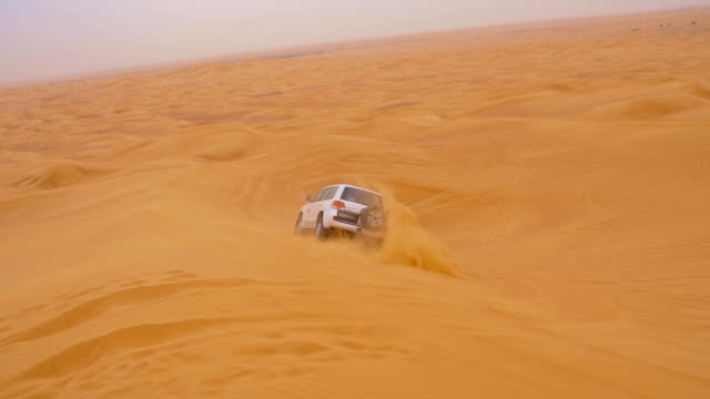 SLO MO Car driving over a dune