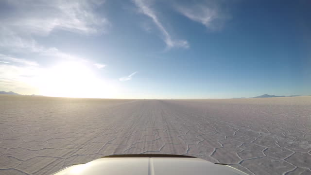 pov car driving over a salt lake in the andean mountains - ウユニ塩湖点の映像素材/bロール