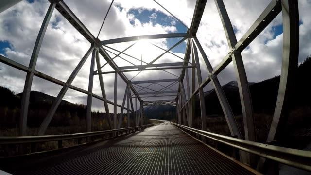 Car driving over suspended bridge in Canada POV