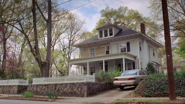 vídeos de stock, filmes e b-roll de ws a car driving past a two story craftsman bungalow with a white picket fence and sedan in the driveway / georgia, united states - entrada para carros