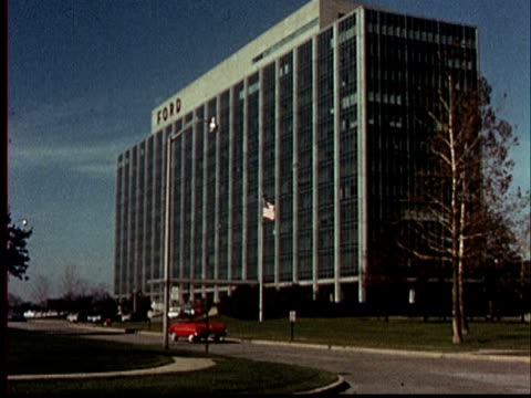 1965 WS Car driving past Ford office building/ WS sign for Ford Research and Engineering Center/ Detroit, Michigan