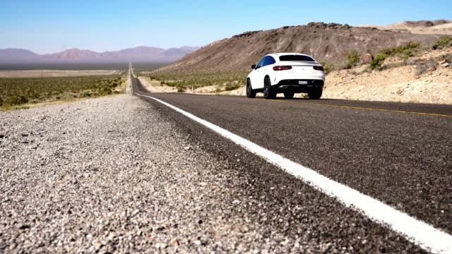 vídeos de stock, filmes e b-roll de ds carros dirigindo através do deserto - estrada