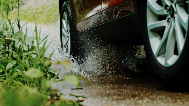 slo mo car driving through a puddle - wheel stock videos & royalty-free footage