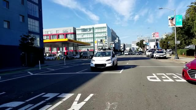 car pov driving through an intersection in san francisco california past a white cruise self driving car from automotive company general motors red... - driverless car stock videos & royalty-free footage