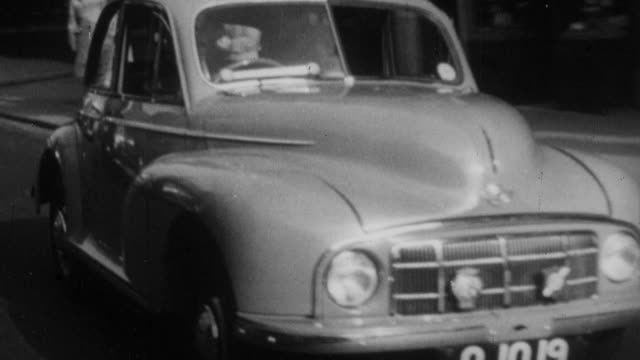 vídeos y material grabado en eventos de stock de 1952 montage car driving through an urban area and parking on the street / england - 1952