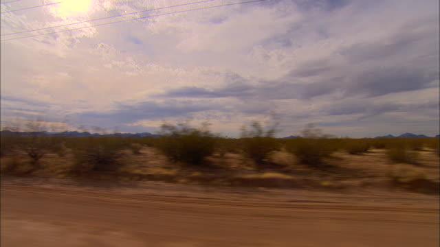 SIDE POV, Car driving through desert, New Mexico, USA