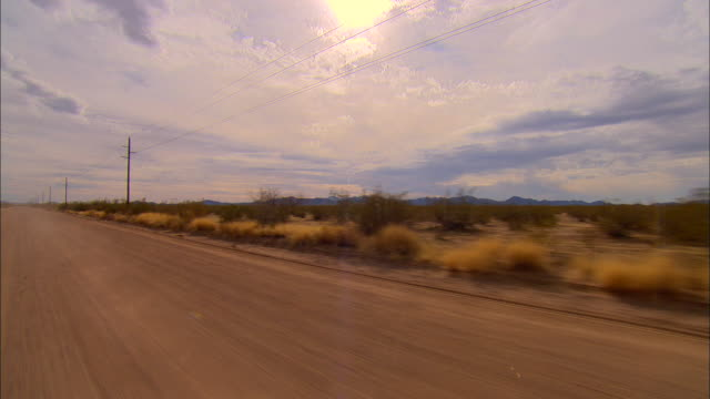 3/4 rear pov, car driving through desert, new mexico, usa - electricity pylon stock videos and b-roll footage
