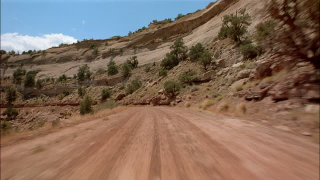 pov car driving through desert - strada in terra battuta video stock e b–roll