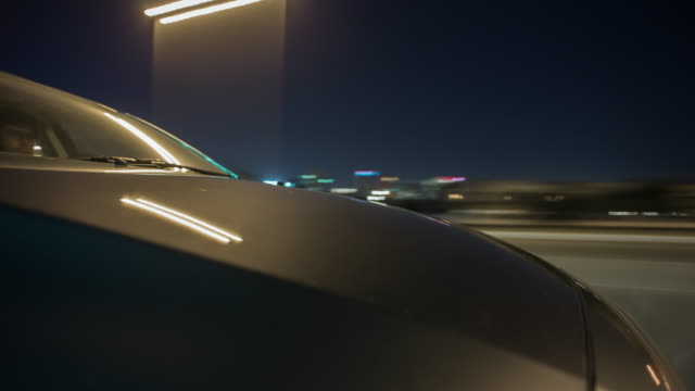 A car driving through Dubai during night with the hood in foreground