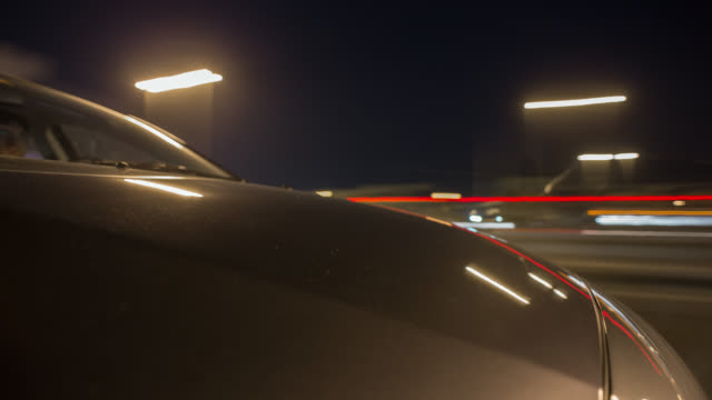 Car driving through Dubai during night with the hood in foreground. Streaking reflections on the car's surface