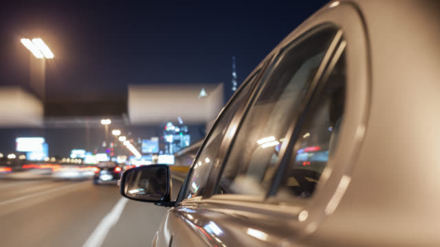 Car driving through Dubai during night with the side of the car in foreground. Streaking reflections on the car's surface