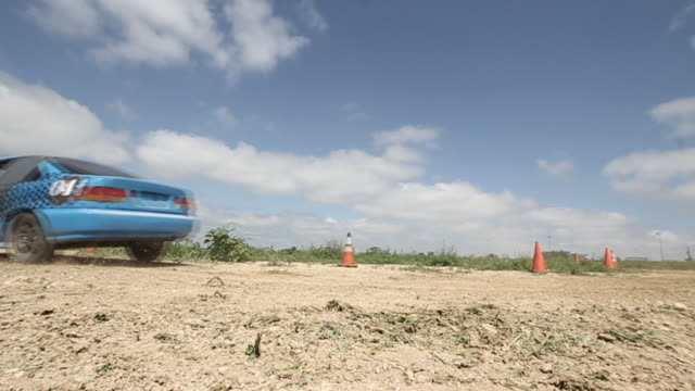 car driving through empty field around cones - 固定撮影点の映像素材/bロール