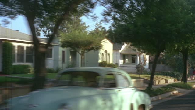 1955 POV Car driving through leafy suburban street as two children ride a bicycle / Los Angeles, United States