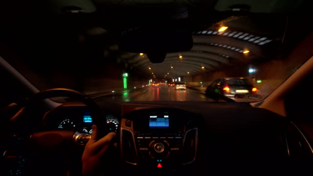 POV Car driving through motorway tunnel during rain