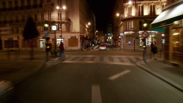 vidéos et rushes de t/l pov car driving through narrow city streets at night, paris, france - signalisation