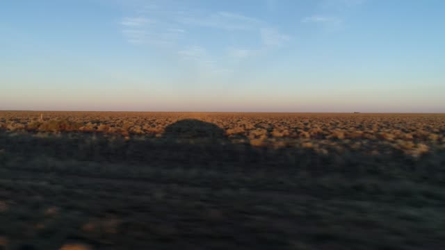 car pov driving through outback desert landscape at sunset - passenger point of view stock videos & royalty-free footage