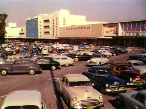 1951 car driving through parking lot of shopping center / industrial