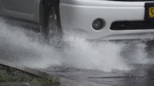 Car driving through puddle during a thunderstorm in New York City in slow motion.