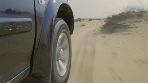 vídeos y material grabado en eventos de stock de cu, pov, suv car driving through sand onto highway - sports utility vehicle