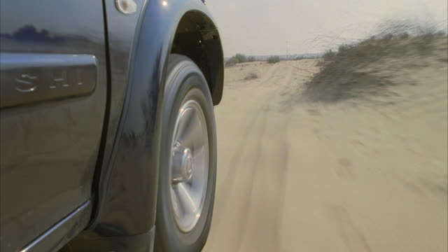 cu, pov, suv car driving through sand onto highway - sports utility vehicle stock-videos und b-roll-filmmaterial
