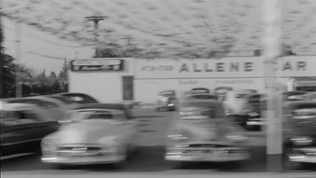 vidéos et rushes de 1955 pov car driving through small business district in southern california / united states - barber shop