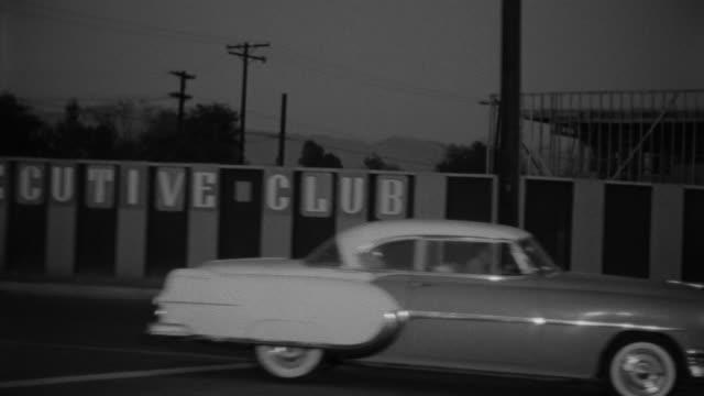 1955 POV Car driving through Toluca Lake district at night / Toluca Lake, Southern California