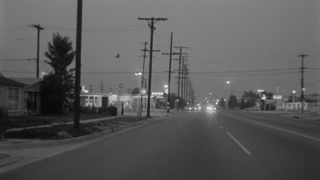 1955 POV Car driving through Toluca Lake district in evening / Toluca Lake, Southern California
