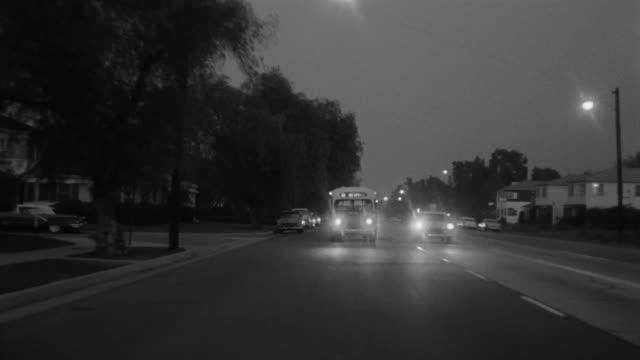 1955 pov car driving through toluca lake district in evening / toluca lake, southern california - 乗物後部から見た視点点の映像素材/bロール