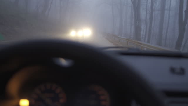 car pov. driving to work in the fog on a highway in the fog during covid-19 pandemic. busy life, traffic is slowed down. - transportation event stock videos & royalty-free footage