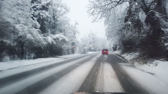 car pov. driving to work in the winter snow on a highway during covid-19 pandemic. busy life, traffic is slowed down. - transportation event stock videos & royalty-free footage