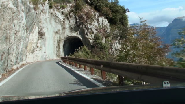 ms pov car driving towards small tunnel part of lake and mountain with narrow street on steep coast / limone, brescia, italy    - narrow stock videos & royalty-free footage