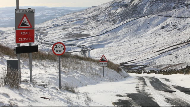 a car driving up kirkstone pass in the lake district, during winter weather, cumbria, uk. - road closed sign stock videos & royalty-free footage
