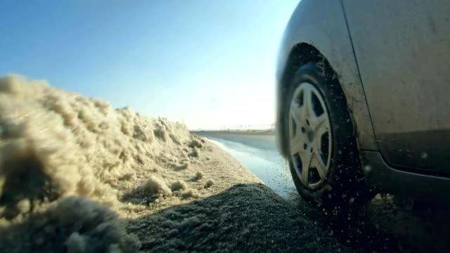 vídeos de stock, filmes e b-roll de carro que conduz pneus do inverno no fim da estrada da neve acima - chegada