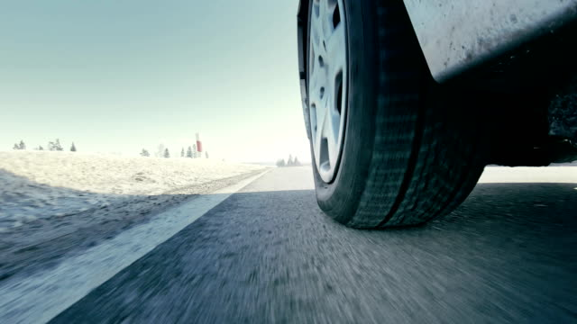 stockvideo's en b-roll-footage met auto rijden winter banden op snow road close up - autoband