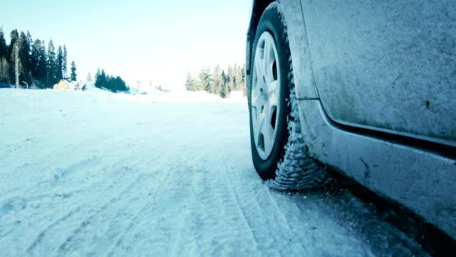 vidéos et rushes de voiture conduisant des pneus d'hiver sur la route de neige près - roue