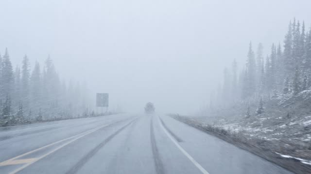 vídeos de stock e filmes b-roll de car driving with heavy snow in blizzard with poor visibility at national park - nevão