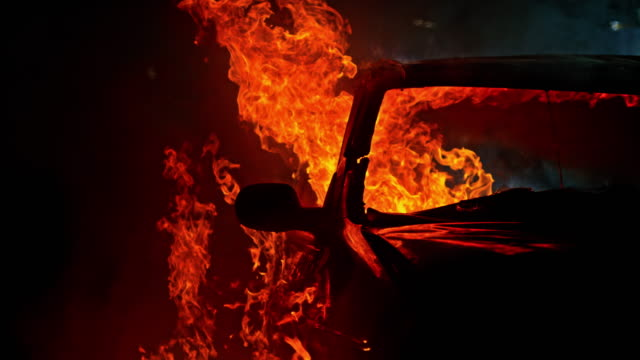 slo mo ld car engulfed by billowing flames at night - bruciare video stock e b–roll